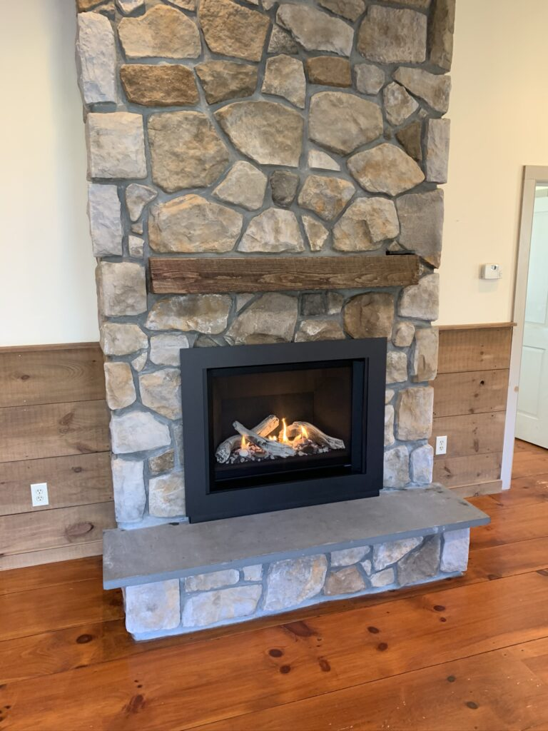 gas fireplace with stone surround and wood shelf